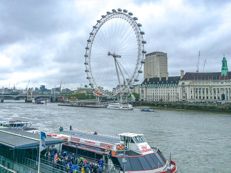 white ferris wheel with river and boat in front one day in london