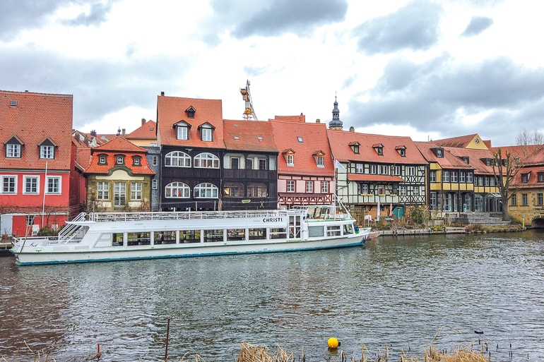 colourful houses lining river with boat in front bamberg germany