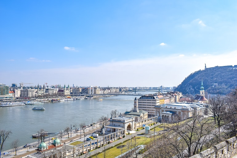 blue sky and river with old buildings lining river bank budapest