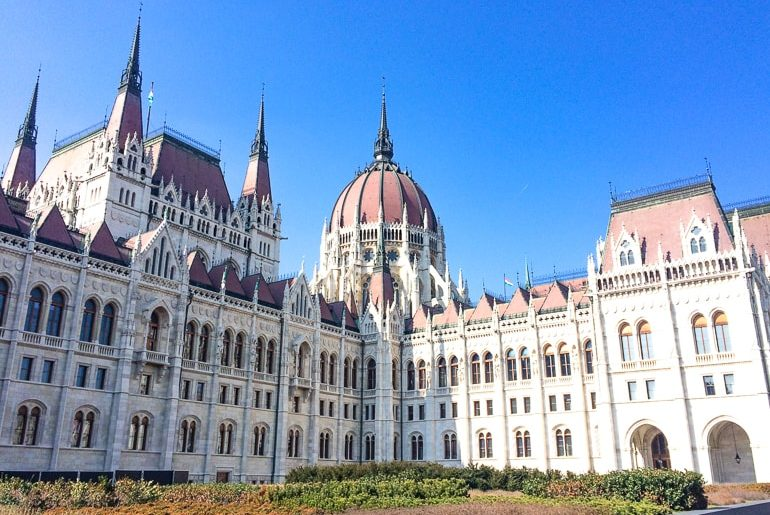 white gothic building with red dome roof hungarian parliament