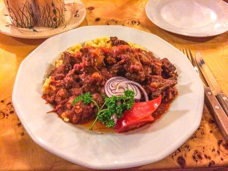 Gulasch in weißem Teller auf Tisch Restaurant Budapest Ungarn