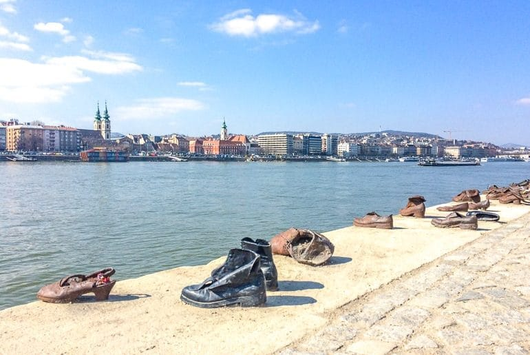 iron shoes on side of river overlooking river bank buildings