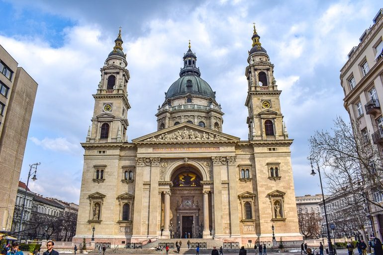 stone church with domes and towers in budapest square
