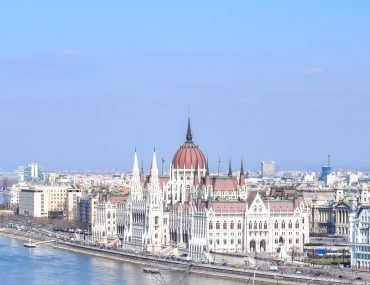 white building with red dome on river bank 3 days in budapest