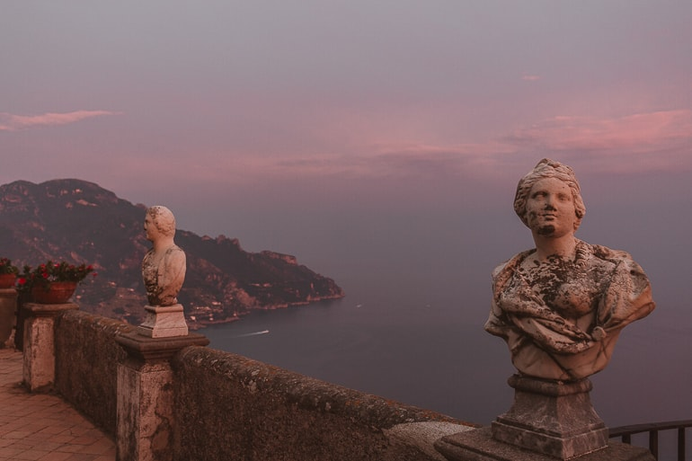 statue heads with scenic overview below in italy