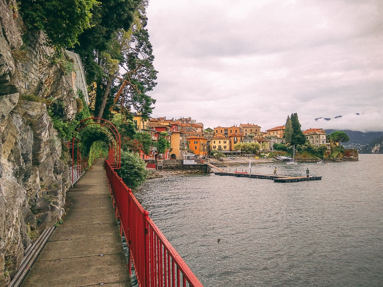 red railing along shoreline with water and seaside town in distance lake como