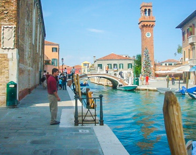 man standing beside water on promenade with tower behind murano