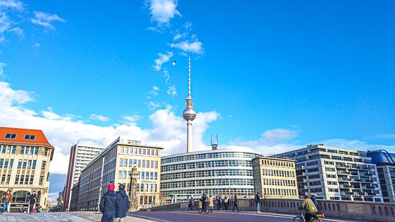 tower over city buildings with blue sky behind one day in berlin