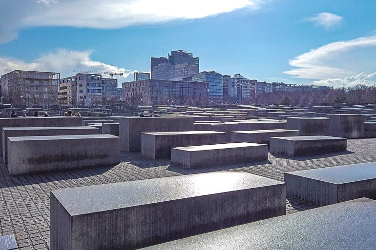 concrete blocks with blue sky behind memorial to murdered jews in berlin