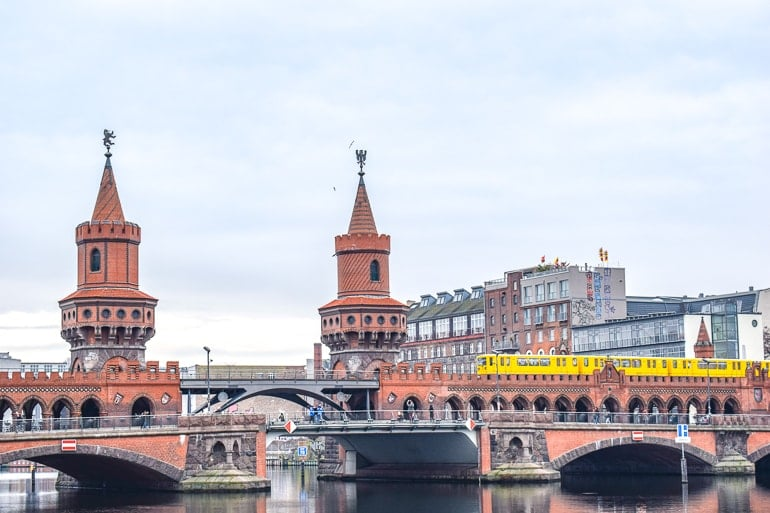 red bridge with two towers over river and yellow train on it berlin