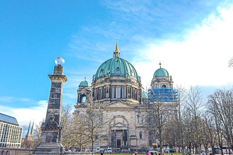church with green domes and blue sky behind berlin dom