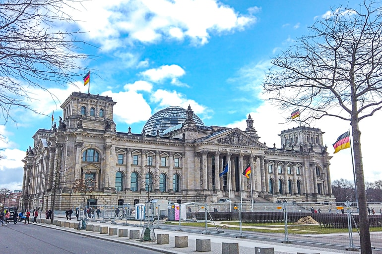 large parliament building with german flags and glass dome on top reichstag one day in berlin