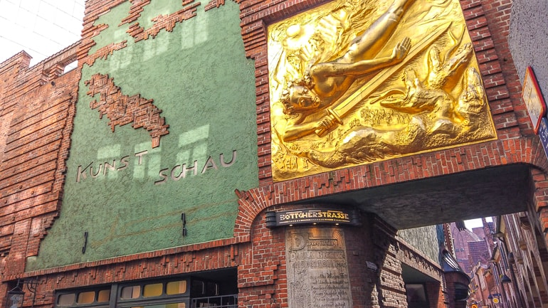 golden statue with red brick alleyway behind bottcherstrasse breman germany