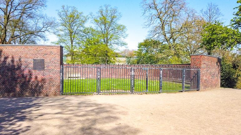 Rotes Denkmal aus Backstein mit eisernem Tor in Park