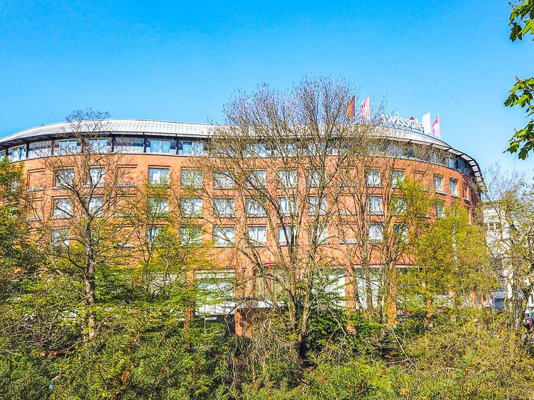 red brick hotel through trees with blue sky swisshotel bremen