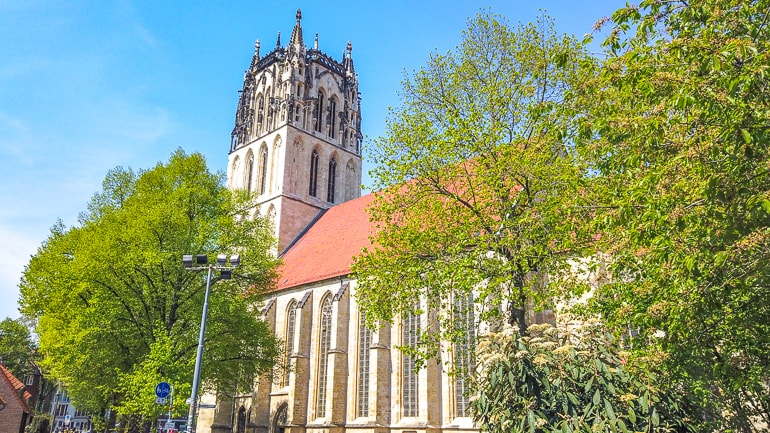church tower with red roof through green trees munster germany