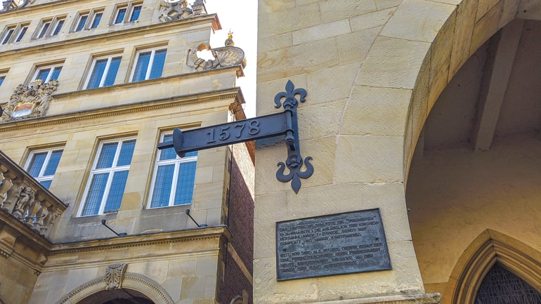 date on metal sign handing from old brick town hall in munster germany