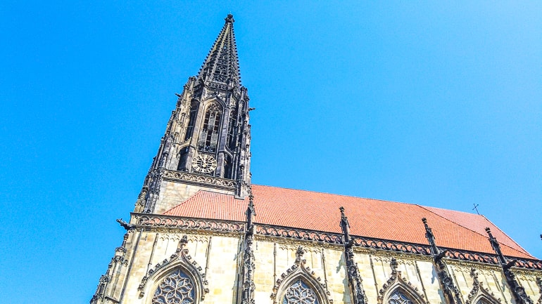 black church tower connected to red roof with blue sky munster germany