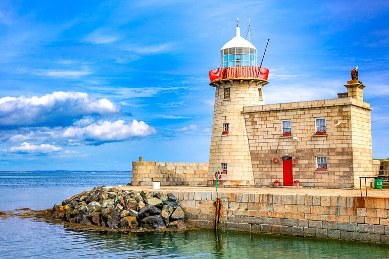 lighthouse on end of pier with blue ocean behind where to stay in dublin howth