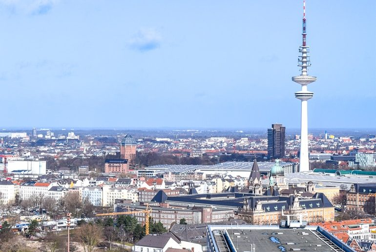 cityscape with tall tower and red brick hotel in distance where to stay hamburg