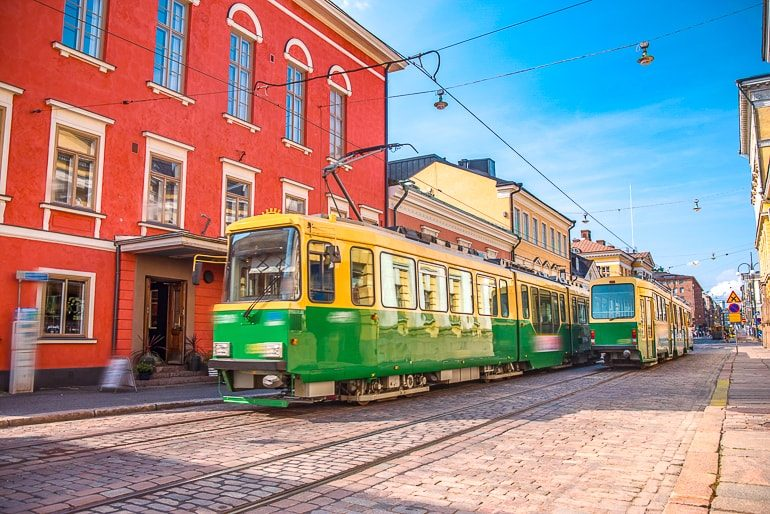 green street cars pass by red building city centre helsinki where to stay