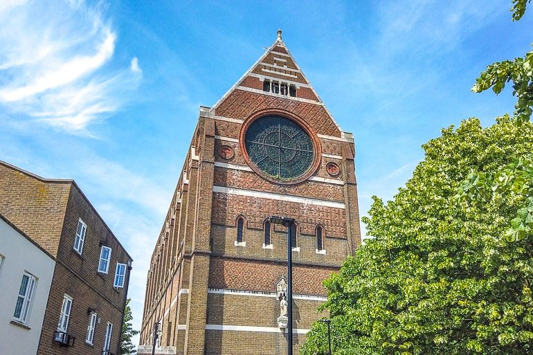 brown brick church with stain glass window and blue sky behind in brighton