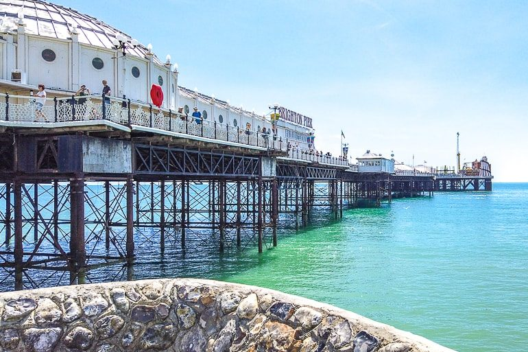 historic pier with wooden supports above blue shoreline in brighton uk