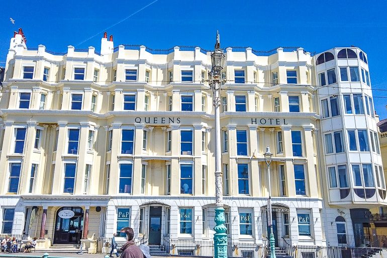 yellow and blue hotel on coastline with blue sky in brighton
