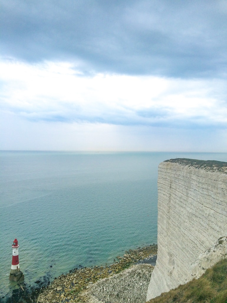 white chalk cliffs with red lighthouse and blue ocean below seven sisters