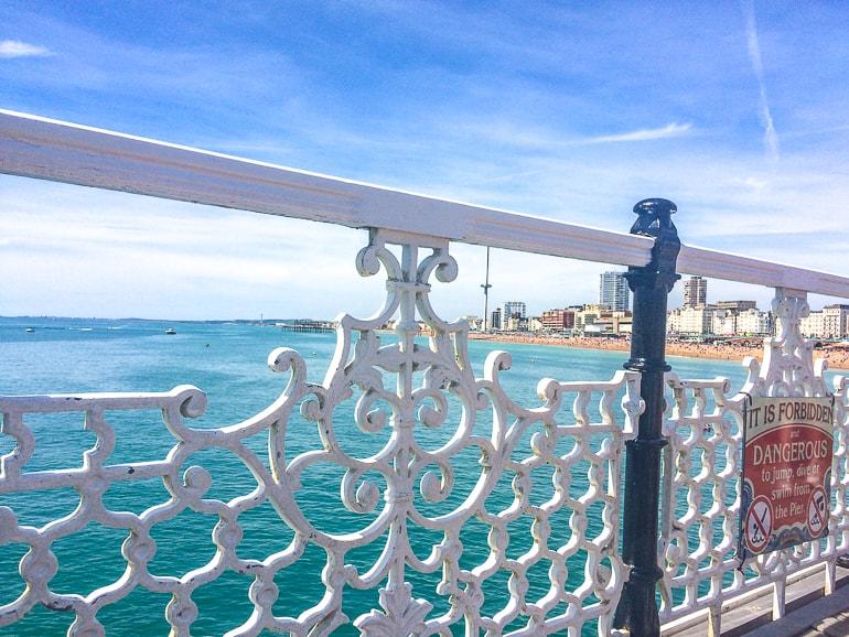 Blaue Küstenlinie durch weißen Zaun des historischen Piers in Brighton