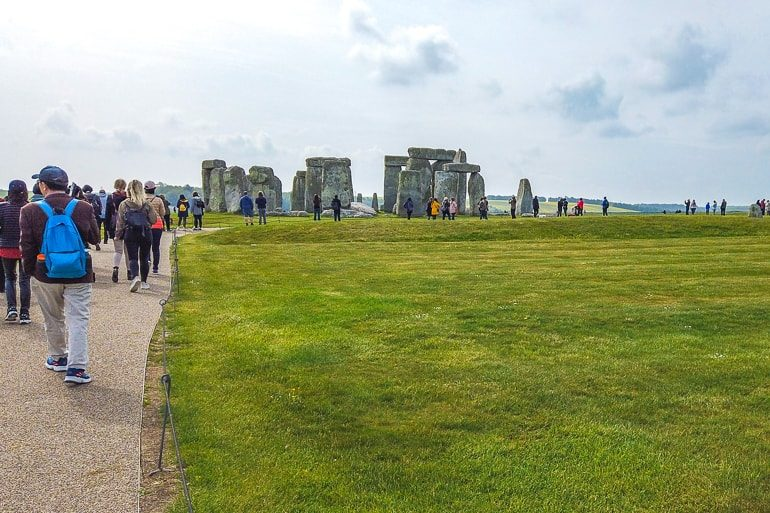 people walking on path towards stonehenge with green grass around