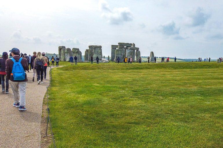 Menschen laufen zu Steinkreis mit grünem Gras in der Umgebung