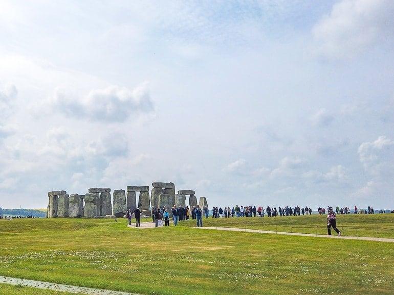 rocks of stonehenge in field with crowds around visiting stonehenge