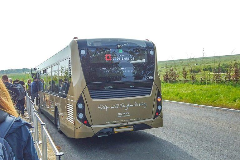 tan shuttle bus on road at stonehenge