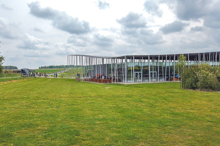 metal poles holding up visitor centre roof with green fields around at stonehenge