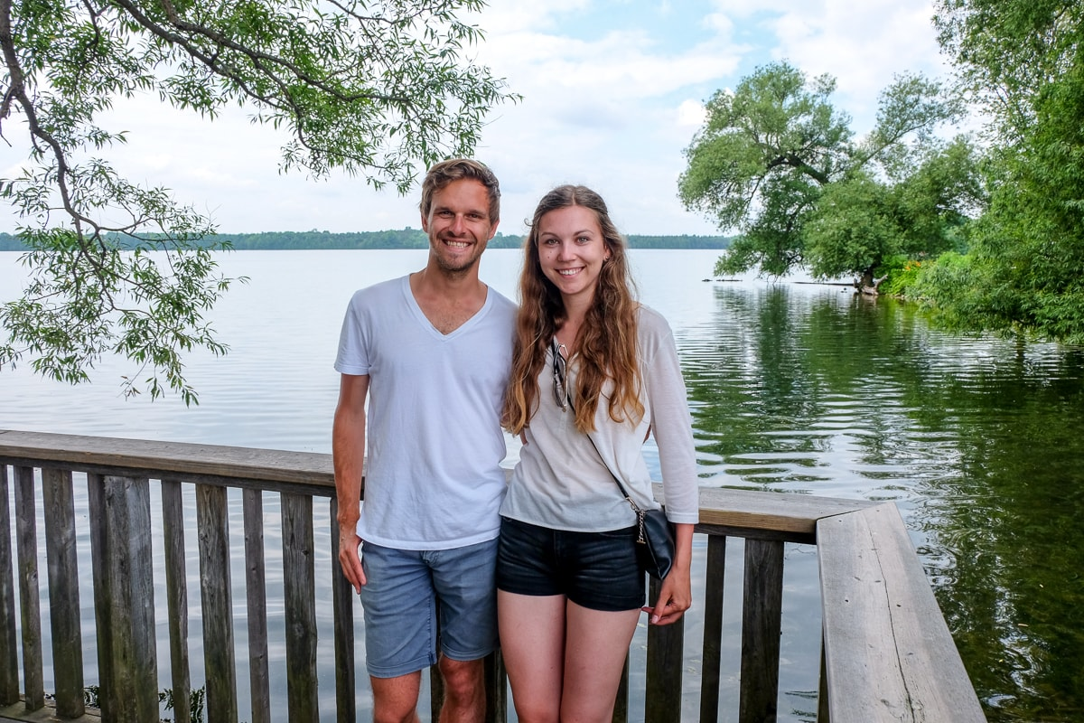Man and Woman posing for photo in front of lake and trees