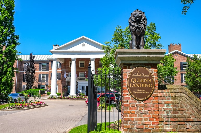 red brick gate to inn with white column entrance behind queens inn niagara on the lake