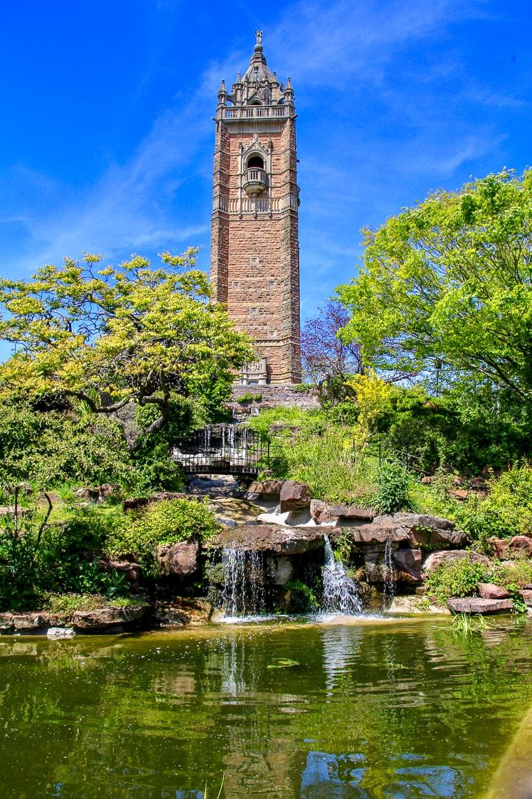 Turm aus Stein mit grünen Bäumen und Fluss im Vordergrund