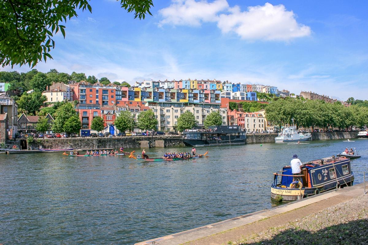 Boot im blauen Fluss mit bunten Häusern im Hintergrund Bristol Attraktionen