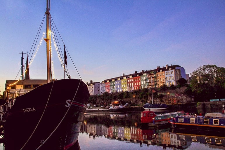 ship at night sitting in water with colourful houses behind bristol harbourside