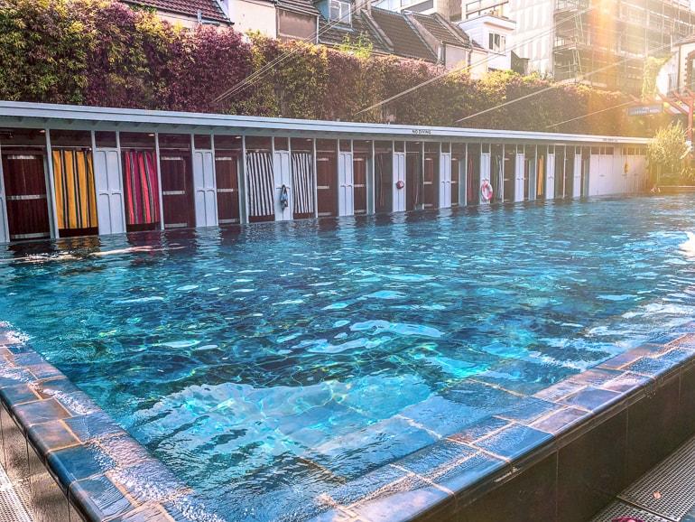 Blauer Pool mit Umkleidekabinen im Sonnenschein Attraktionen Bristol