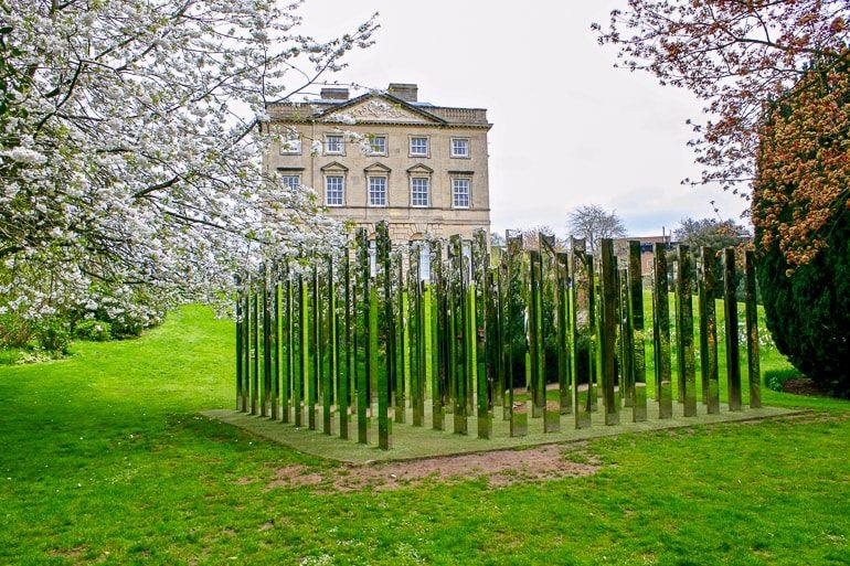 Historisches Gebäude mit grünem Rasen und Labyrinth aus Spiegeln