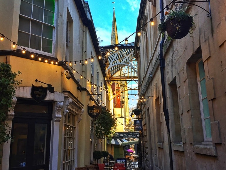 alleyway lit up at night with spire in background bristol market