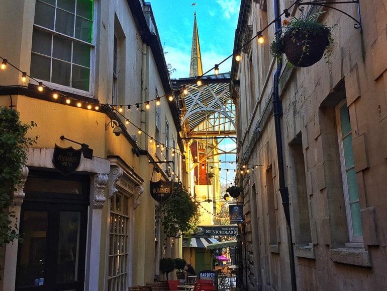 Gasse beleuchtet am Abend mit Turm im Hintergrund Bristol