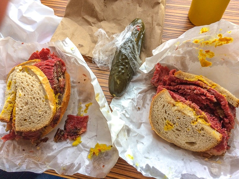 meat sandwiches on paper with green pickle between things to do in montreal