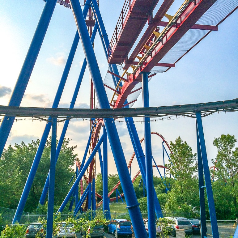blue supports underneath a red track roller coaster at la ronde park in montreal