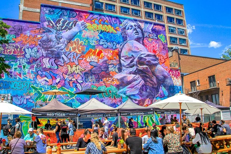 colourful mural on wall with people sitting below muralfest montreal