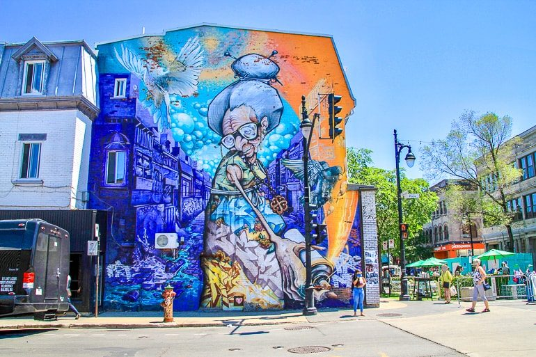 colourful blue wall mural on street corner in montreal at muralfest