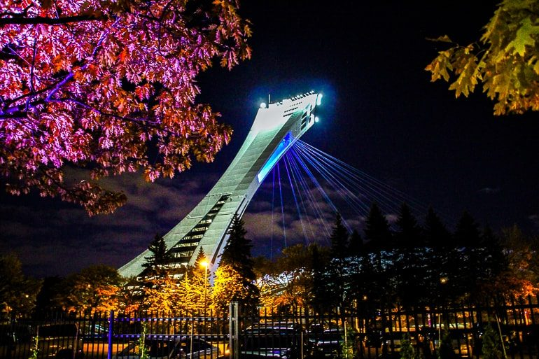 white arena tower with lights through trees in montreal olympic park