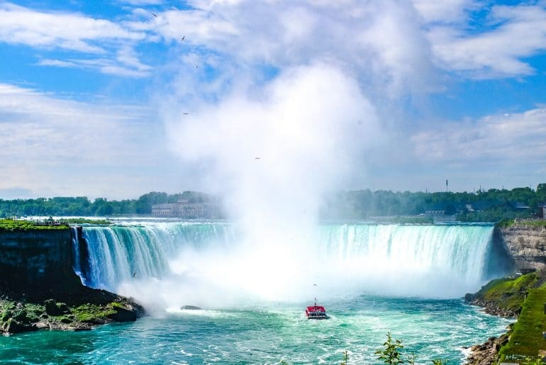 ship sailing toward large blue waterfall things to do in niagara falls canada